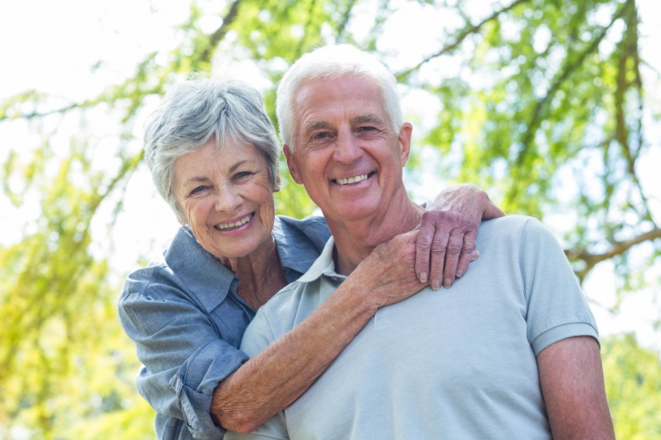 elderly couple with arms around each other