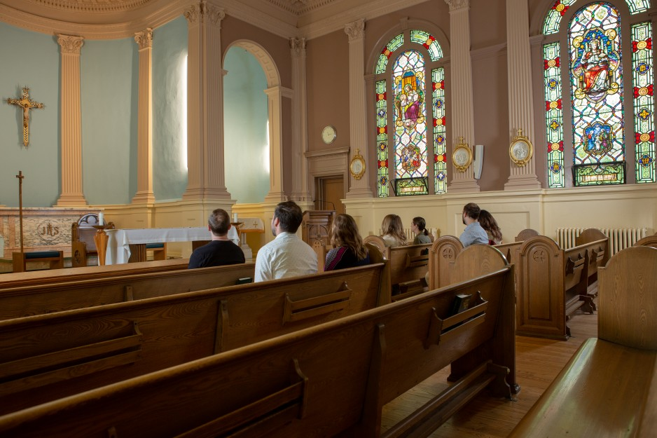 People sit in the pews within the chapel at St. Joseph's Hospital.
