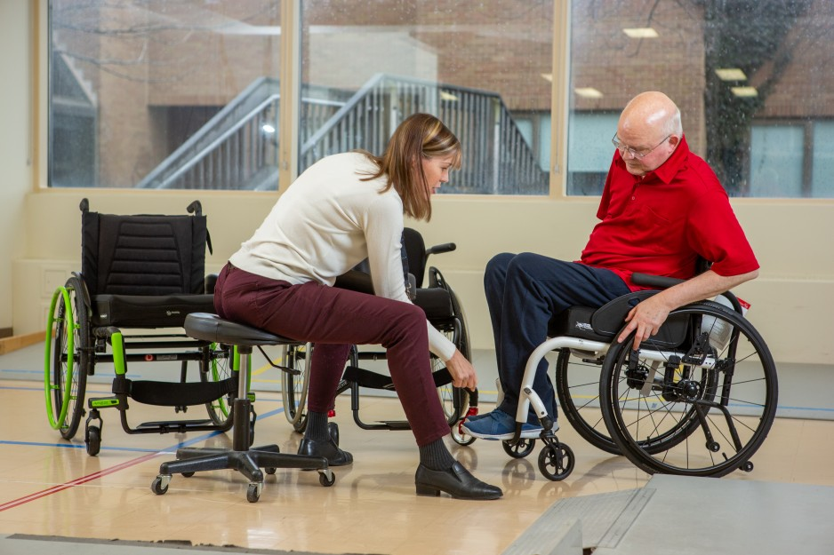A rehabilitation caregiver helps a patient with his wheelchair.