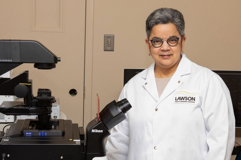 scientist standing beside confocal microscope