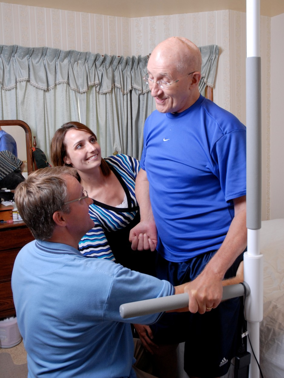A stroke patient undergoes rehabilitation with the help of care providers.