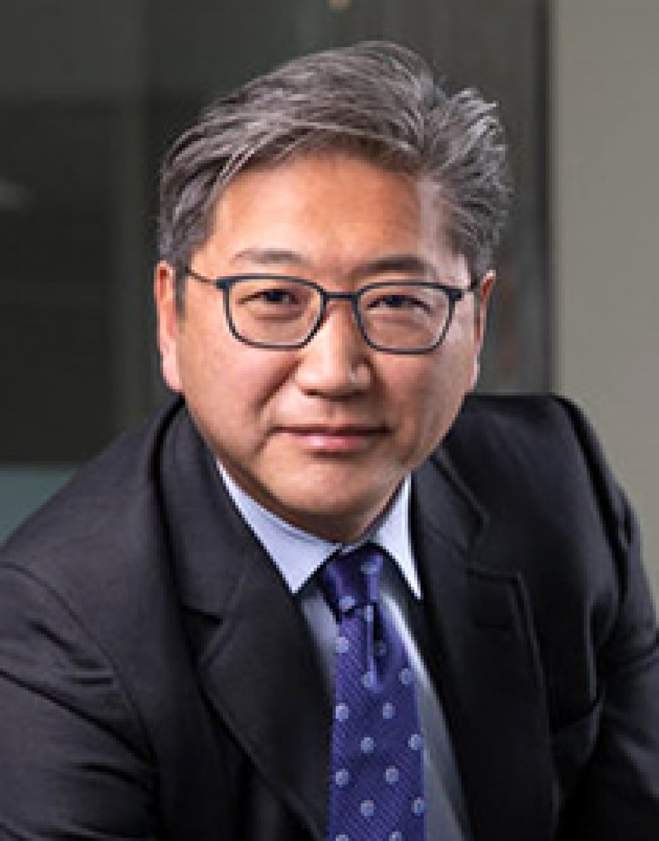 Man wearing suit, tie and glasses.