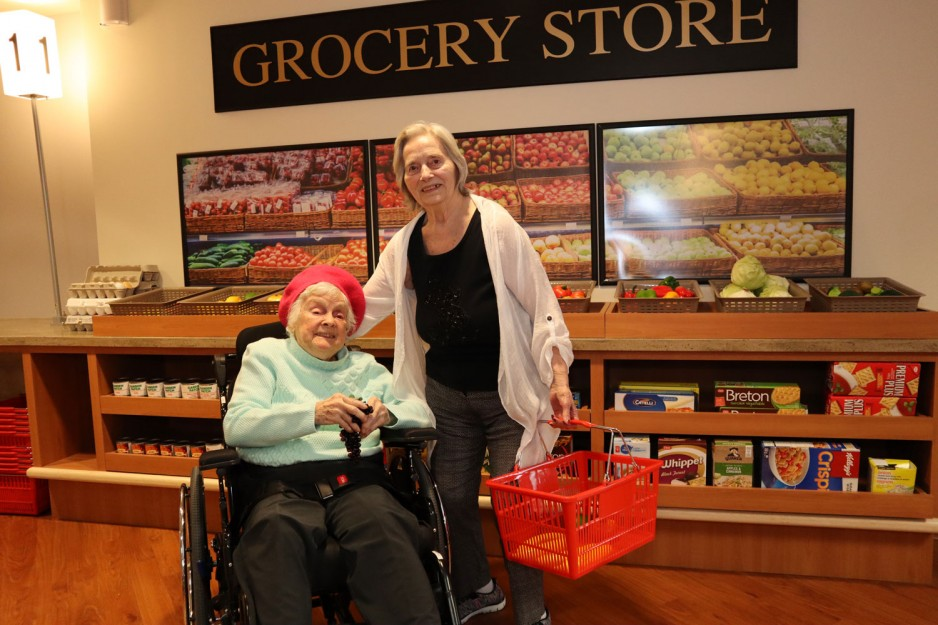 two elderly women in front of grocery store at the interactive village