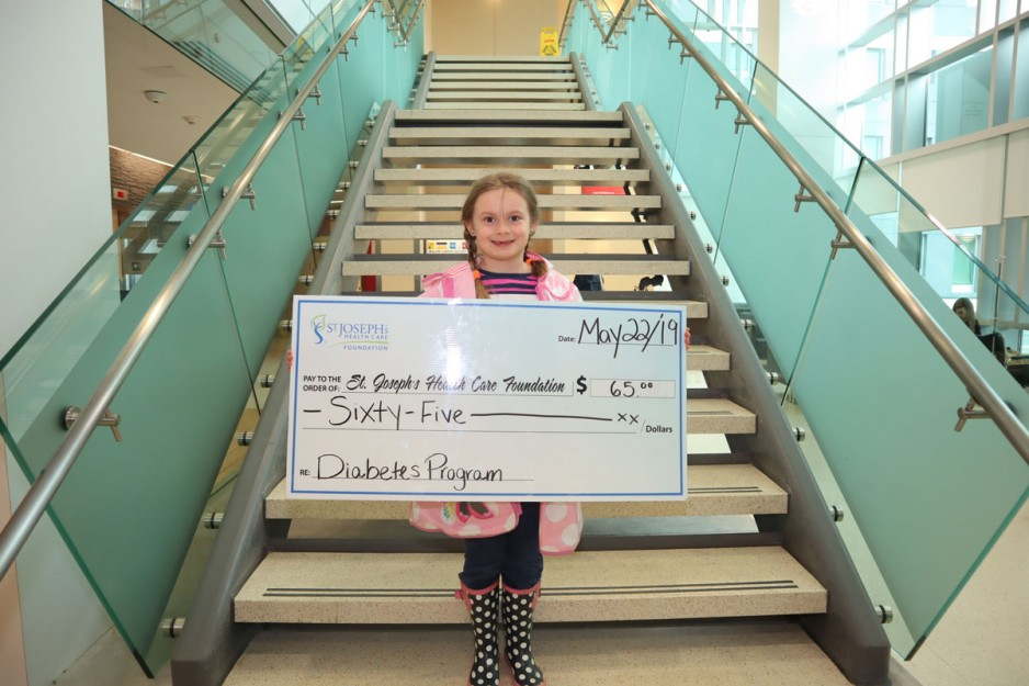 a small girl holds up a large cheque