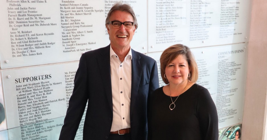 Keith Trussler and Michelle Campbell in front of donor wall