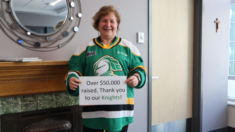 Dr Gillian Kernaghan wears a London knights jersey and holds up a sign thanking the hockey team