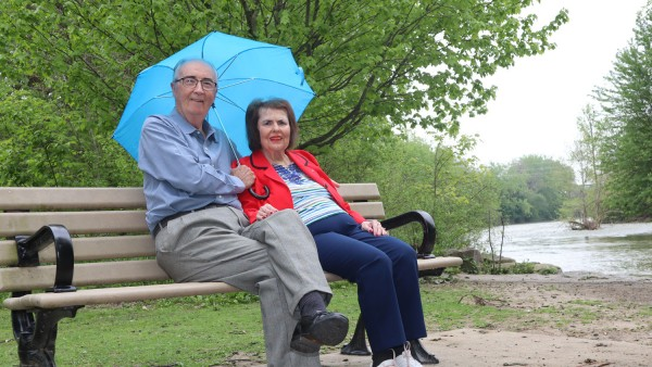 couple sitting on a park bench with an umbrella