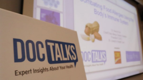 DocTalks sign in front of screen