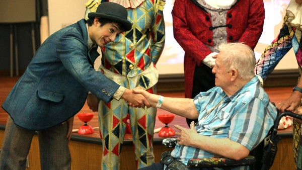 Bob Armstrong shakes the hand of a Cirque du Soleil clown