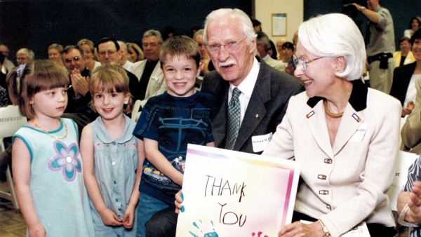 Elderly couple holds up a thank you sign given to them by three children