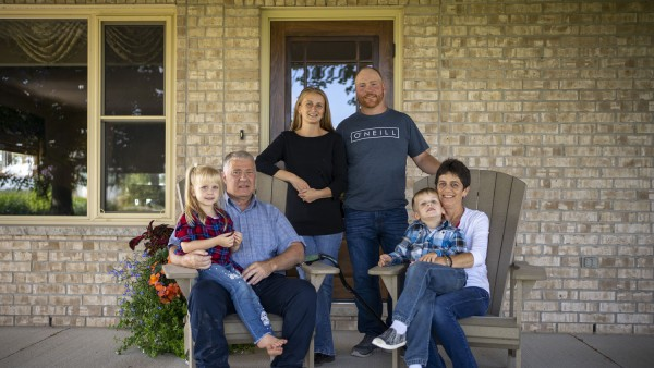 Chris and Connie MacGregor and their family sitting on their porch