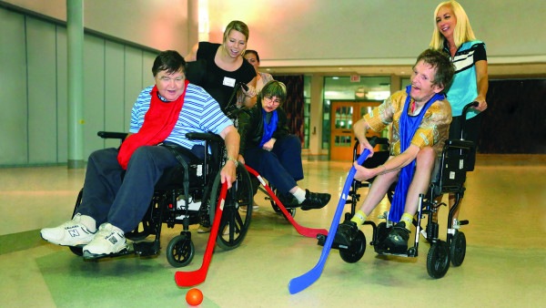 Residents play floor hockey in wheelchairs