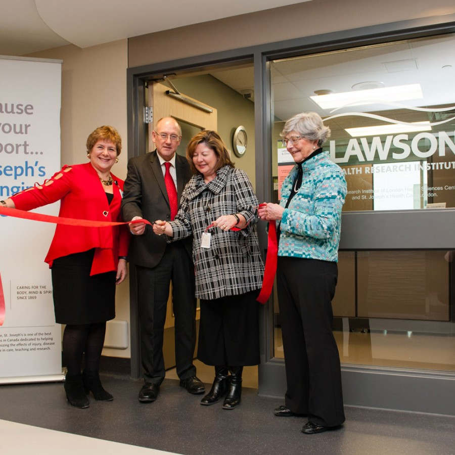 group of people cutting a red ribbon at centre opening